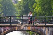 AMSTERDAM - JULY 17: Woman take pictures standing near bicycle on bridge. Bicycles are most used mod