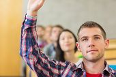 Close-up of a young male student raising hand by others in a row at the classroom