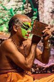 KOCHI, INDIA - FEBRUARY 24, 2013: Unidentified Kathakali exponent preparing for performance by apply