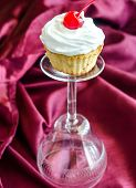 Cupcake With Whipped Cream And Maraschino Cherry