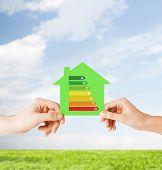 energy saving, real estate and family home concept - closeup of couple hands holding green paper hou