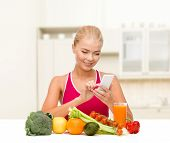 dieting, food, healthcare and technology concept - smiling sporty woman with fruits and vegetables c