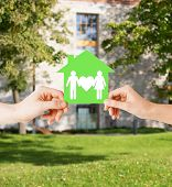 real estate and family home concept - isolated picture of male and female hands holding green paper