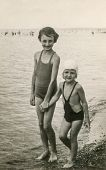 BALATONSZABADI, HUNGARY, CIRCA AUGUST 1937: Vintage photo of two little girls in bath suits at lakes