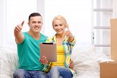 moving, home, technology and couple concept - smiling couple relaxing on sofa with tablet pc compute