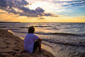 pic of horizon  - Teenaged boy watching the sunset over the watery horizon - JPG