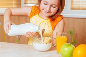 Girl Pours Milk For Healthy Breakfast