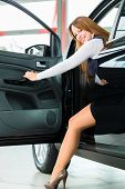 Young woman sits in new car on driver seat in a car dealership, obviously she is buying the auto