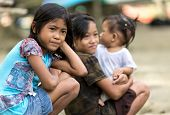 EL NIDO, PHILIPPINES, JANUARY 11 : Kids of a poor filipino family are sitting outdoor, one is holdin