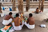 MADURAI, INDIA - FEBRUARY 16, 2013: Indian brahmin (traditional Hindu society) priest and pilgrims i