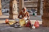 MADURAI, INDIA - FEBRUARY 16, 2013: Indian brahmin (traditional Hindu society) priest with donation