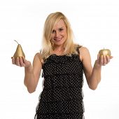 Beautiful woman in a stylish black dress holding golden fruit in her hands displaying the pear and a