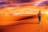 Active woman trekking along desert, walking alone in the dune, discovering nature, expedition to the wilderness, travel and tourism concept
