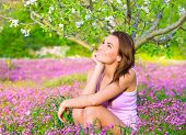Dreamy woman spending time in blooming park, enjoying first blossom of nature, happy weekend in countryside, relaxation outdoors