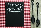 Today's Special on chalkboard with cast iron spoon and fork and red checkered tablecloth