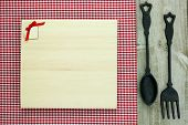 Blank wood menu sign with cast iron spoon and fork on red checkered tablecloth