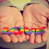 a young man holding in his hands letters painted as the gay pride flag forming the word love, with a