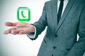 picture of voip  - a businessman with a telephone icon in his hand depicting the voice - JPG