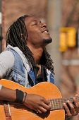 picture of rasta  - young African American musician playing guitar outside - JPG