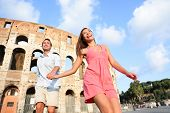 Travel Couple in Rome by Colosseum running fun and romantic holding hands in Italy. Happy lovers on