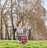 Senior in wheelchair gesturing happiness in park shot with tilt and shift lens
