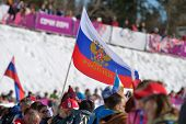 KRASNAYA POLYANA, SOCHI, RUSSIA - FEBRUARY 13, 2014: Russian fans with national flag on the cross-co
