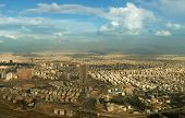 stock photo of tehran  - Aerial view of Tehran city against blue sky with fluffy white clouds shot above Milad Tower - JPG