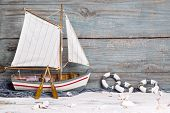 Sailboat or fishing boat made of wood as nautical decoration on wooden background
