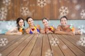 Cheerful people with drinks in swimming pool against snowflakes