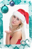 Composite image of a Woman wearing santa hat as she blows kiss against christmas frame