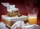 Tissue box in knit encasement and hot flu medicine drink over dark red background