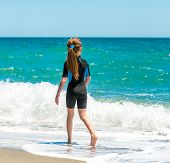 little girl in a wetsuit walking on the seashore. back view