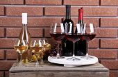 Bottles and glasses of wine and ripe grapes on box on brick wall background