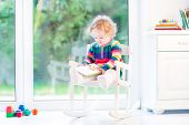 Adorable Curly Girl With Curly Hair Wearing Colorful Knitted Dress Reading In A White Rocking Chair