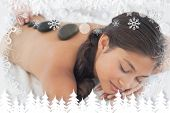 Beautiful brunette enjoying a hot stone massage against fir tree forest and snowflakes