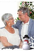 Composite image of a Senior couple in love in Christmas against snow falling