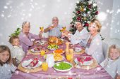 Composite image of Family raising their glasses at christmas against snow falling