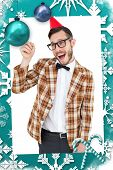 Geeky hipster in party hat pointing against christmas frame