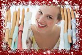 Happy female customer amid clothes rack against snow