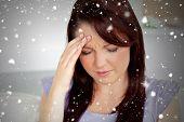 Beautiful woman having a headache sitting on a sofa against snow falling