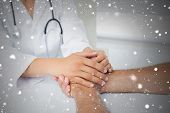 Close up mid section of a doctor holding patients hands against snow falling