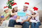 Composite image of Family exchanging Christmas gifts against snow
