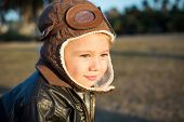 Cute little boy pilot wearing aviator hat and jacket