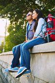 Romantic travelers with rucksacks having rest in park