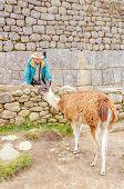 Machu Picchu, Peru - senior tourist and llama in ruins