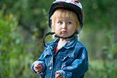Cute little girl with sport helmet for bicycle, roller or skate