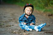 little girl on roller skates sitting on road in the park