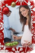Pregnant woman preparing a salad in the kitchen against christmas themed page