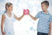 Smiling brother and sister holding piggy bank together against snow falling