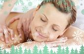 Charming woman enjoying a back massage against snowflakes and fir trees in green